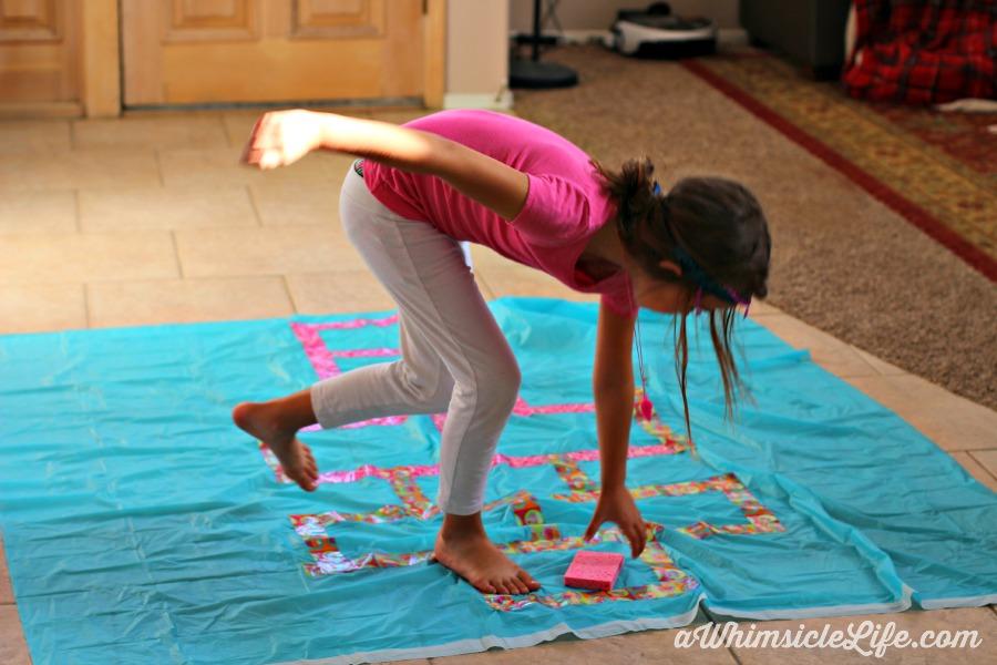 Girl picking sponge off of homemade hopscotch board.