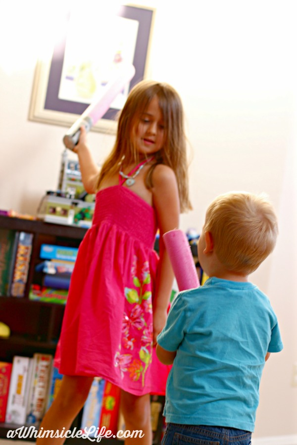 Girl fighting brother with light saber,