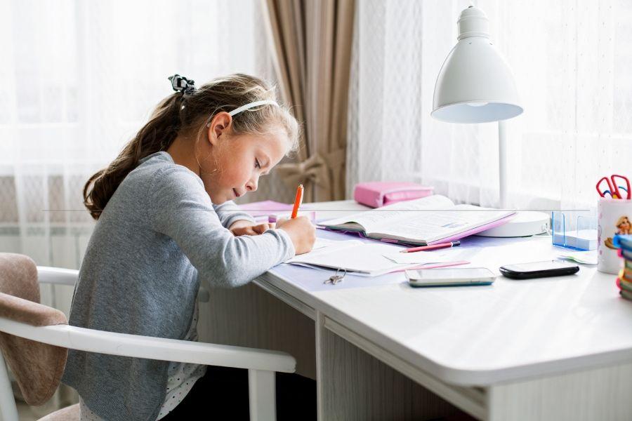 Elementary School girl takes responsibility for doing her own homework.